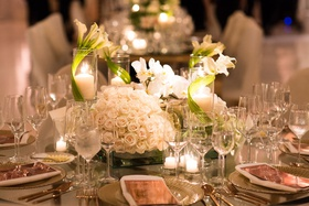 Round table with low arrangements of white roses, orchids, and calla lilies wrapped pillar candles