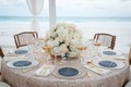 Ocean view tent wedding reception table sequins low centerpiece gold rim glasses wood chairs island