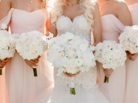 Bridesmaid bouquets with white blush roses and bride bouquet with rose, ranunculus, orchids