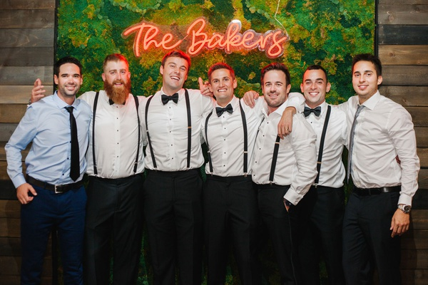 wedding reception moss photo booth backdrop neon sign groom groomsmen in suspenders bow ties