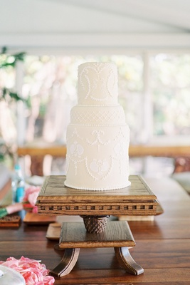 Unique cake with white design on wood pedestal