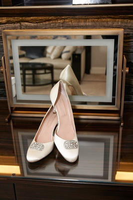 white wedding day heels with crystal detail in front of a mirror