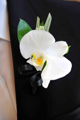 Single white flower and palm fronds on lapel