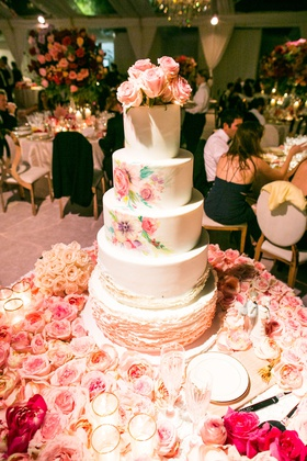 wedding cake with ruffle layers and watercolor design tier fresh roses on top