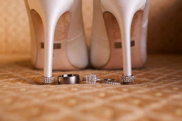 wedding detail shot white bridal heels shoes jewel heel platinum wedding band halo engagement ring
