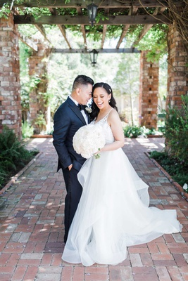 wedding portrait brick flooring and wood beams greenery black tuxedo and hayley paige wedding dress