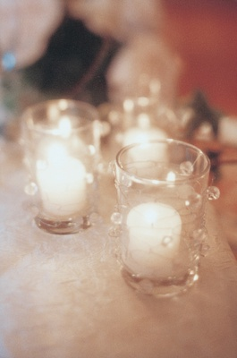 white candles in glass votives