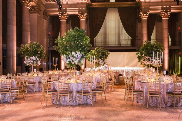 Ballroom wedding with tree centerpieces and gold chairs