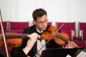 Man playing violin at church wedding ceremony