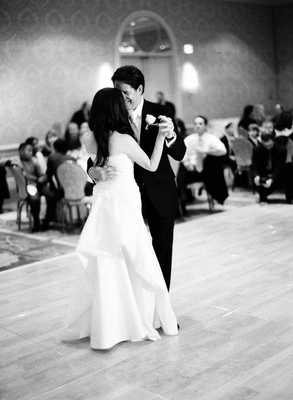 Bride in a Pronovias gown with a bustle train dances with groom in black tuxedo