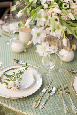 white and gold charger plates with pink and green flowers green table linens white candles