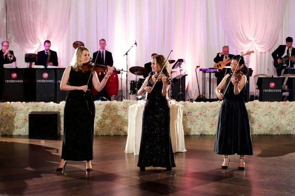 Three women in black dresses playing the violin fiddle at wedding reception live band ivory flowers