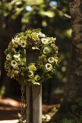 Green and brown rustic wedding wreath at entrance