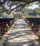 Outdoor wedding ceremony decorations flower petal aisle, flower markers on wood chairs, floral gates