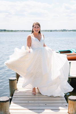 bride in striped hayley paige wedding dress twirling on private dock