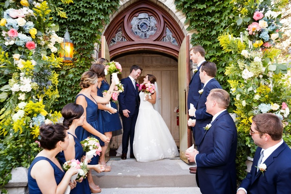 Bride and groom at top of stairs outside church with bridesmaids and groomsmen in navy blue