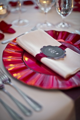 red charger with wavy ridges on edge, cream napkin with scarlet velvet ribbon