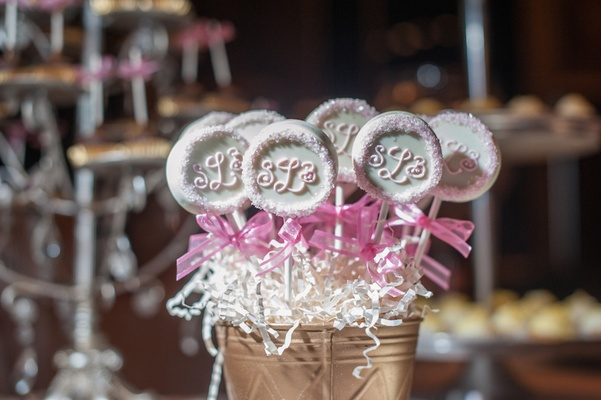 Wedding reception dessert table with the couple's monogram on pastry pops in a golden bucket