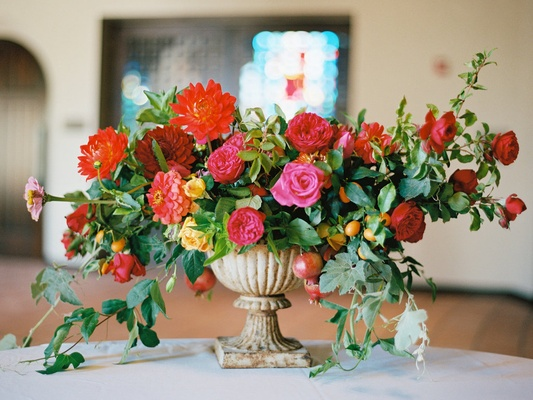 Wedding ceremony flower arrangement in stone urn with red, orange, pink, and yellow flowers