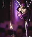 Silver tree decorated with purple flowers and candles