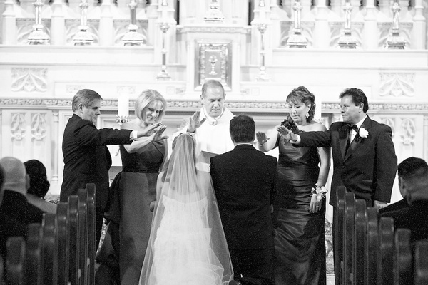 Black and white photo of priest and parents blessing couple