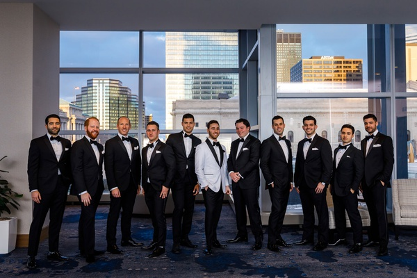 groom in white tuxedo jacket black bow tie groomsmen in black and white suits tuxes