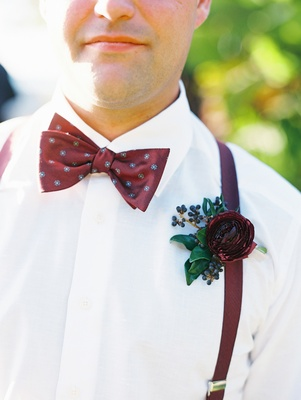 groomsman with burgundy boutonniere, bow tie, and suspenders