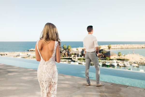 bride in sexy yolancris backless wedding dress walks up to groom for first look