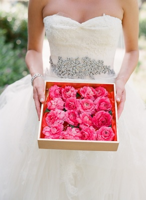 Bride holds box full of pink flower boutonniere