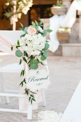 Wedding ceremony white chair pink ribbon sash garden rose reserved sign die cut outdoor ceremony