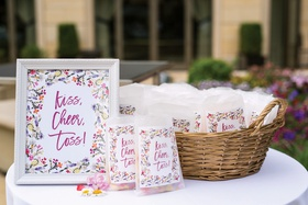 "framed floral-print sign reading ""kiss, cheer, toss!"" next to bags of petals"