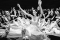 black and white photo of bride hands on dance floor friends grabbing pieces of wedding dress skirt
