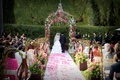 ceremony in garden with pink rose petals on aisle and pink and green floral canopy