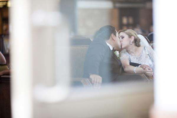 Bride in beaded Jenny Packham dress kisses groom in black tuxedo