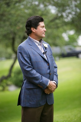 Groom in a plaid blazer, patterned shirt, espresso pants, and gardenia boutonniere