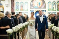 Bride in monique lhuillier wedding dress groom in navy tuxedo bow tie flowers white hydrangea on pew