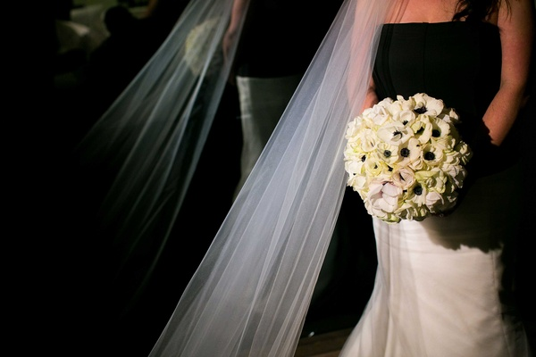 bride in a gown with a black bodice and white skirt holding a bouquet of white amaryllis