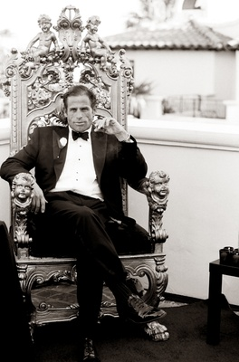 Black and white photo of groom sitting on king's throne