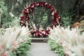 circle ceremony arch made with marsala and blush flowers, aisle lined with pampas grass