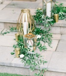 italian ruscus at base of unique gold lanterns