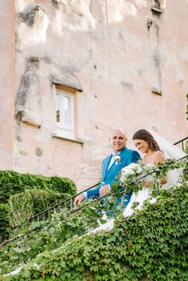 Bride in veil and wedding dress walking down steps vine covered staircase with dad in blue jacket