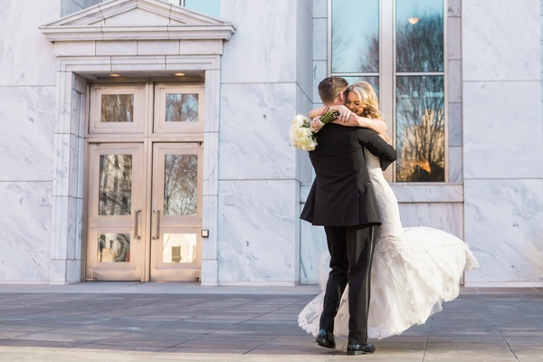 Josh hugs and lifts bride after their first look photography session