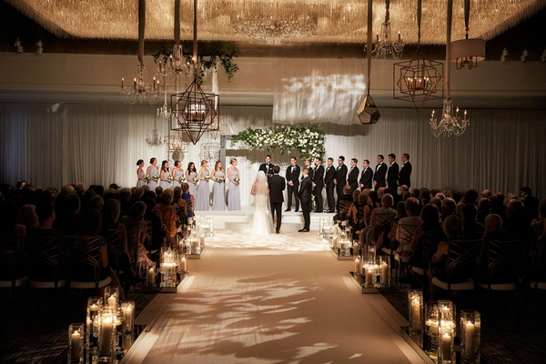 wedding ceremony ballroom chandeliers bridesmaids groomsmen guests wide aisle lanterns archway