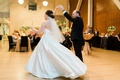 bride in justin alexander plain ball gown spun by groom in menguin suit during first dance