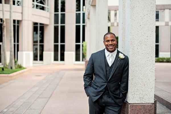 African American man in tuxedo leaning against pillar