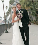 Bride and groom smile near docks in California