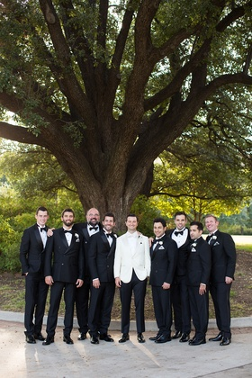 Groom in black pants and white tuxedo bow tie with groomsmen in traditional tuxedos