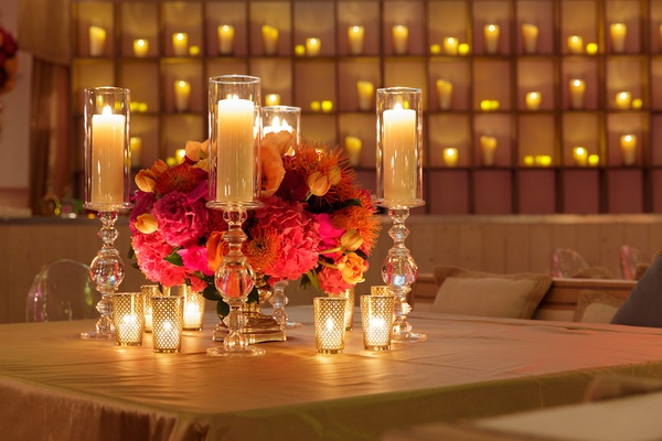 Wedding weekend welcome dinner with a wall of candles and candles in decorative crystal holders