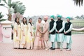 bridesmaids in yellow, bride in blush sari, groomsmen in turquoise, sikh ceremony