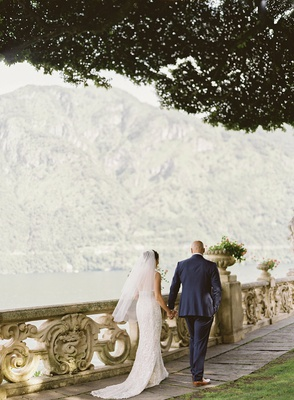 lake como wedding portrait bride and groom walking along railing by lake under tree